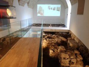 Particolare della illuminazione dei resti archeologici sotto la passerella e visione anche della videoproiezione sullo sfondo nella sala 6