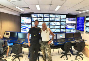 Due colleghi in Control Room davanti alla parete monitoria e alla postazione dei controllori di gara della FOM!
